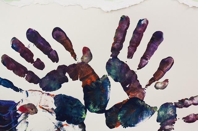 Pintura plasmando las palmas de las manos juntas en color sobre un lienzo